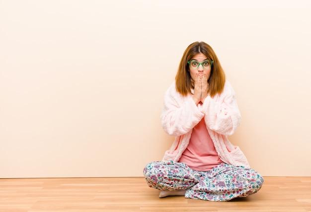 Tragende pyjamas der jungen frau, die zu hause fühlen gesorgt, gestört und erschrocken sitzen, mund mit den händen bedecken, besorgt schauen und oben verwirrt haben