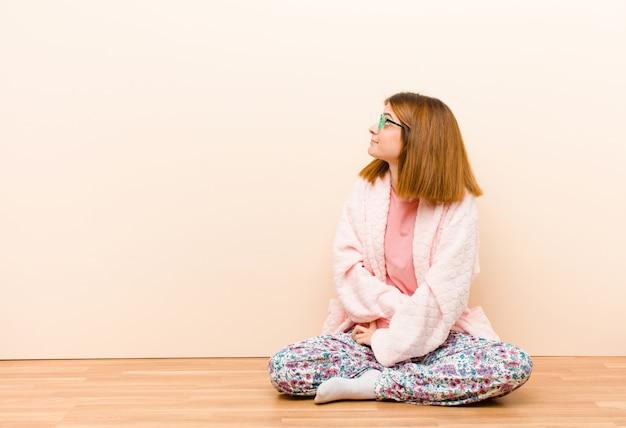 Tragende pyjamas der jungen frau, die zu hause fühlen verwirrt oder voll oder die zweifel und fragen, wundernd, mit den händen auf hüften, hintere ansicht sitzen