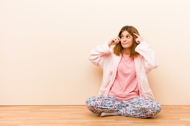 Tragende pyjamas der jungen frau, die zu hause fühlen verwirrt oder zweifelnd sitzen, sich auf eine idee konzentrieren, stark denken und schauen zum copyspace auf seite