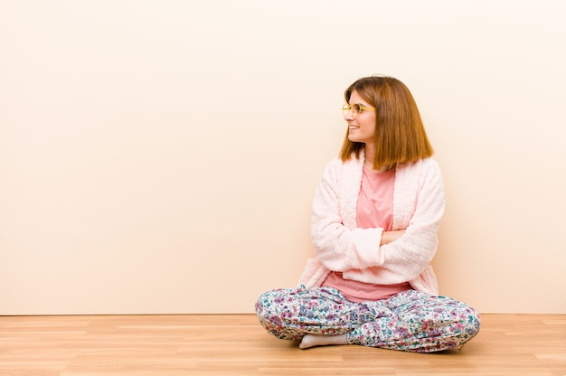 Tragende pyjamas der jungen frau, die zu hause lächeln mit den gekreuzten armen und einem glücklichen, überzeugten, erfüllten ausdruck, seitenansicht sitzen