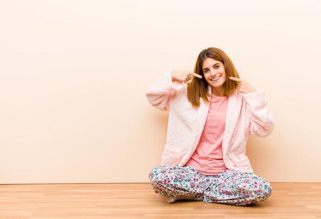 Tragende pyjamas der jungen frau, die zu hause lächeln sitzen, sicher zeigend auf eigenes breites lächeln, positive, entspannte, erfüllte haltung