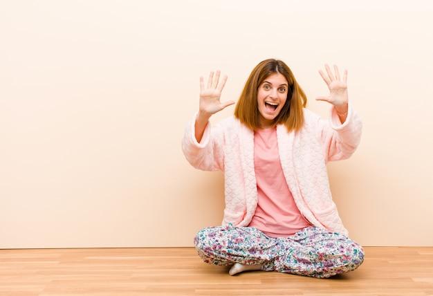 Tragende pyjamas der jungen frau, die zu hause lächeln und schauen freundlich sitzen und zeigen nr. zehn oder zehntel mit der hand vorwärts und zählen unten