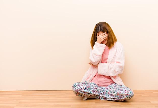 Tragende pyjamas der jungen frau, die zu hause schauen betont, beschämt oder gestört, mit kopfschmerzen, gesicht mit der hand bedeckend sitzen