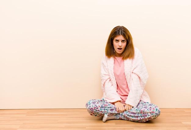Tragende pyjamas der jungen frau, die zu hause schauen entsetzt, verärgert, gestört oder enttäuscht, mit offenem mund und wütend sitzen