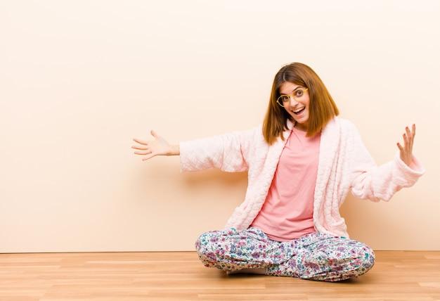Tragende pyjamas der jungen frau, die zu hause schauen glücklich, arrogant, stolz und selbstzufrieden sitzen und wie eine nr. eine glauben