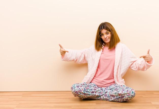 Tragende pyjamas der jungen frau, die zu hause schauen stolz, arrogant, glücklich, überrascht und zufrieden sitzen und zeigen auf das selbst und fühlen sich wie ein sieger