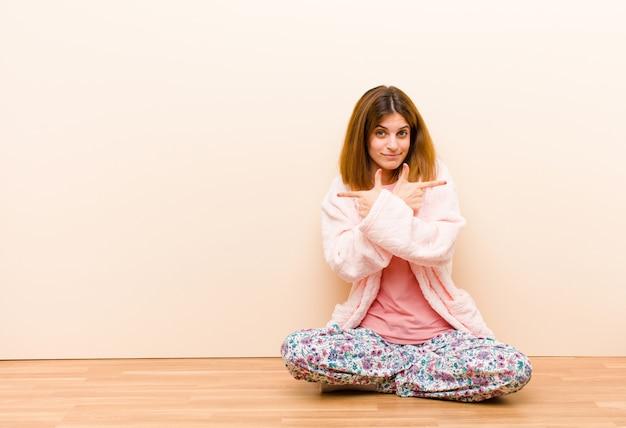 Tragende pyjamas der jungen frau, die zu hause schauen verwirrt und verwirrt, unsicher sitzen und in entgegengesetzte richtungen mit zweifeln zeigen