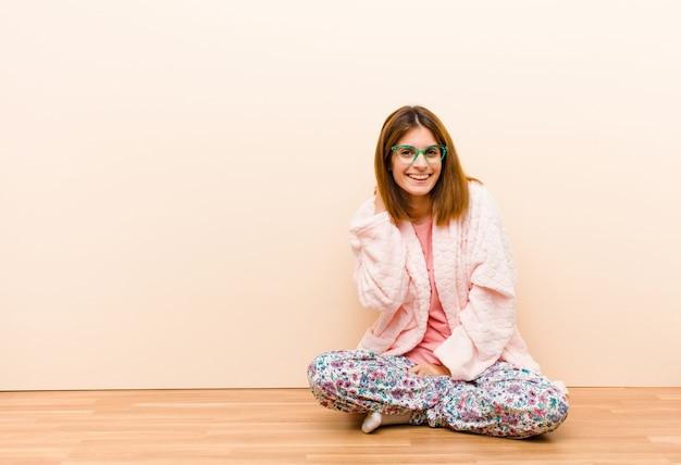 Tragende pyjamas der jungen frau, die zu hause sitzen, fröhlich und sicher mit einem zufälligen, glücklichen, freundlichen lächeln lachend