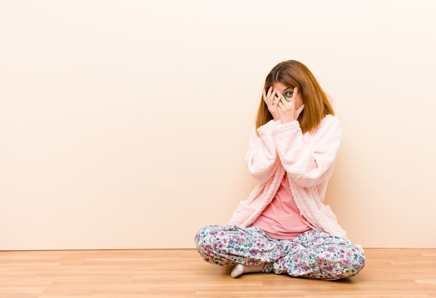 Tragende pyjamas der jungen frau, die zu hause sitzen, fühlend erschrocken oder verlegen, spähend oder mit den augen ausspionierend, die mit den händen halb bedeckt sind
