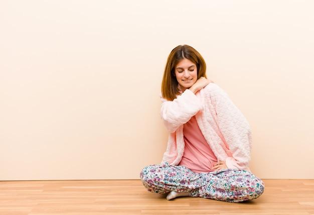Tragende pyjamas der jungen frau, die zu hause sitzen, fühlend müde, betont, besorgt, frustriert und deprimiert und leiden mit rücken- oder nackenschmerzen
