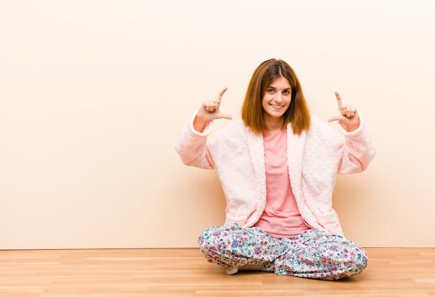 Tragende pyjamas der jungen frau, die zu hause sitzen, gestalten oder eigenes lächeln mit beiden händen umreißen, die positives und glückliches wellnesskonzept schauen