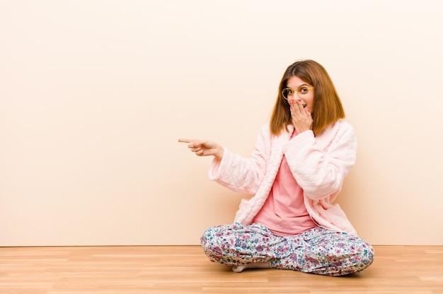 Tragende pyjamas der jungen frau, die zu hause sitzen, glücklich, entsetzt und überrascht sich fühlen, mund mit der hand bedecken und auf seitliches copyspace zeigen
