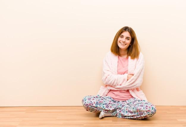 Tragende pyjamas der jungen frau, die zu hause sitzen, glücklich lachend mit den armen gekreuzt, mit einer entspannten, positiven und erfüllten haltung
