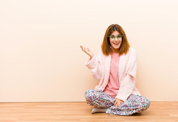Tragende pyjamas der jungen frau, die zu hause sitzen, glücklich, überrascht und nett sich fühlen, lächelnd mit der positiven haltung und verwirklichen eine lösung oder eine idee