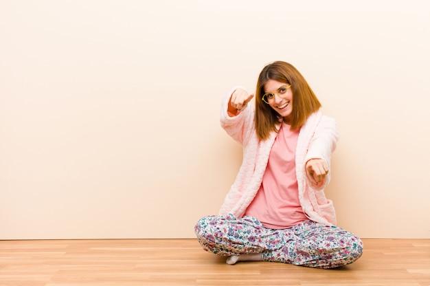 Tragende pyjamas der jungen frau, die zu hause sitzen, glücklich und überzeugt sich fühlen, auf kamera mit beiden händen zeigen und lachen und sie wählen