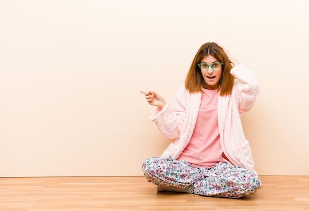 Tragende pyjamas der jungen frau, die zu hause sitzen, lachen, glücklich, positiv und überrascht schauen und eine großartige idee verwirklichen, die auf seitlichen kopienraum zeigt