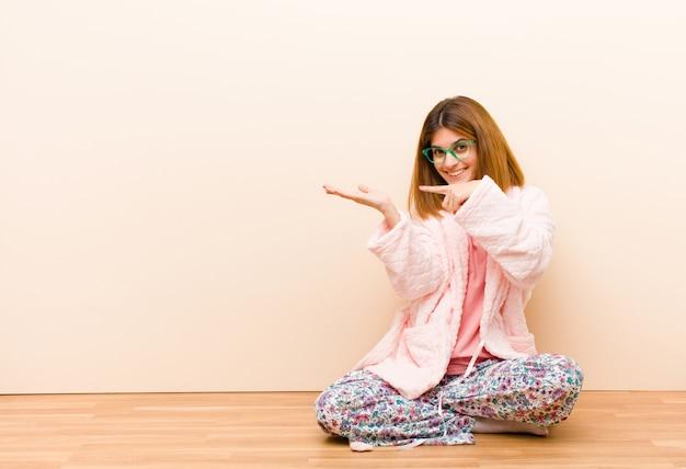Tragende pyjamas der jungen frau, die zu hause sitzen, nett lächeln und zeigen, um raum auf palme auf der seite zu kopieren, einen gegenstand zu zeigen oder zu annoncieren