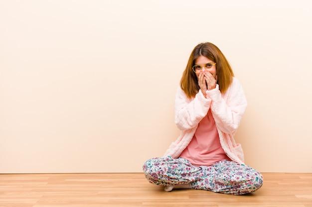 Tragende pyjamas der jungen frau, die zu hause sitzen, schauend glücklich, nett, glücklich und überrascht, mund mit beiden händen bedeckend