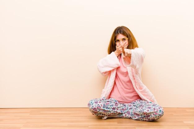 Tragende pyjamas der jungen frau, die zu hause sitzen, über sie lachen, auf kamera zeigen und sich über sie lustig machen oder sie verspotten