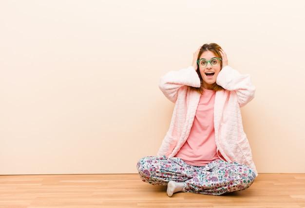 Tragende pyjamas der jungen frau, die zu hause sitzen und hände zum kopf anheben, mit offenem mund, sich extrem glücklich, überrascht, aufgeregt und glücklich fühlend