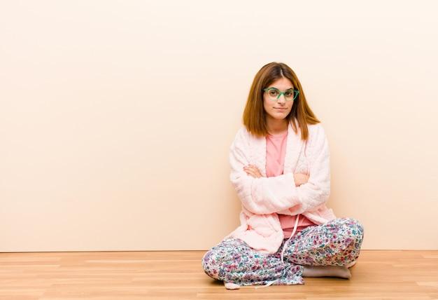 Tragende pyjamas der jungen frau, die zu hause sitzen und missfallen und enttäuscht schauen ernst gestört und verärgert mit den gekreuzten armen