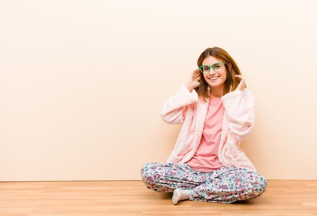 Tragende pyjamas der jungen frau, die zu hause sitzen und nett und zufällig lächeln, hand nehmend, um mit einem positiven, glücklichen und überzeugten blick voranzugehen