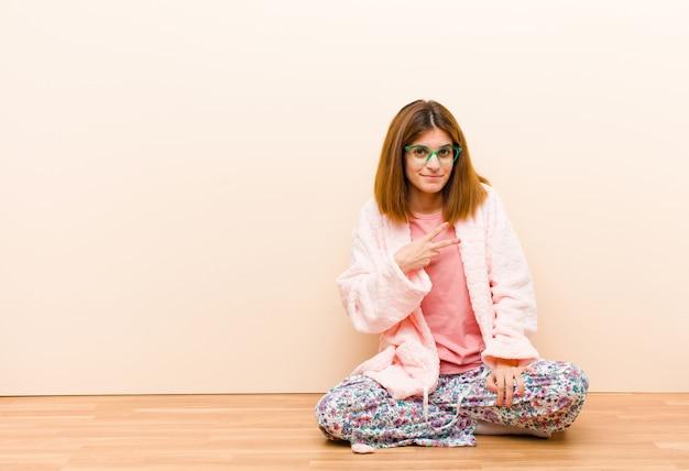 Tragende pyjamas der jungen frau, die zu hause sitzen und sich glücklich, positiv und erfolgreich fühlen, wenn die hand v-form über kasten macht, sieg oder frieden zeigt