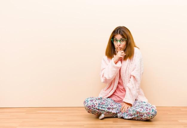 Tragende pyjamas der jungen frau, die zu hause sitzen und um ruhe bitten und mit dem finger vor dem mund gestikulieren, der shh sagt oder ein geheimnis hält