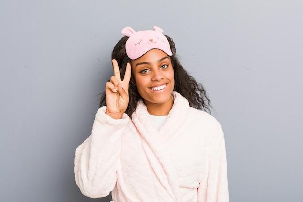 Tragende pyjamas der jungen frau und eine schlafmaske, die siegeszeichen zeigt und breit lächelt