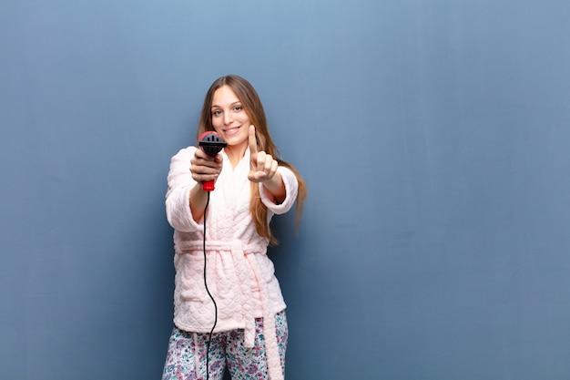 Tragende pyjamas der jungen hübschen frau und halten eines friseurs