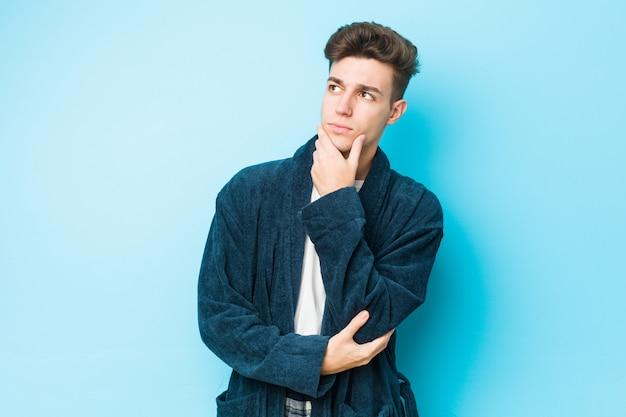 Tragende pyjamas des jungen kaukasischen mannes, die seitlich mit zweifelhaftem und skeptischem ausdruck schauen.