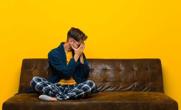 Tragende pyjamas des jungen mannes, die augen mit den händen mit einem traurigen, frustrierten blick der verzweiflung, schreiend, seitenansicht bedecken. auf einem sofa sitzen