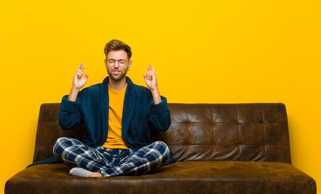 Tragende pyjamas des jungen mannes, die besorgt beide finger kreuzen