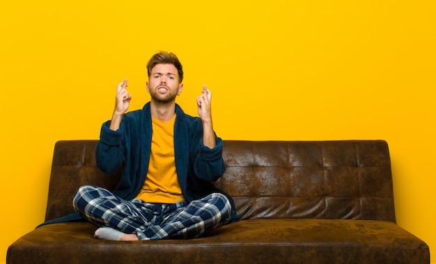 Tragende pyjamas des jungen mannes, die besorgt finger kreuzen und auf gutes glück mit einem besorgten blick hoffen. auf einem sofa sitzen