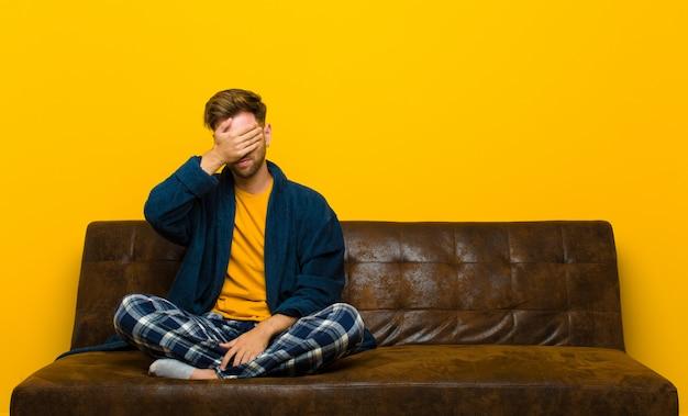Tragende pyjamas des jungen mannes, die betont, beschämt oder gestört, mit kopfschmerzen, gesicht mit der hand bedeckend schauen. auf einem sofa sitzen