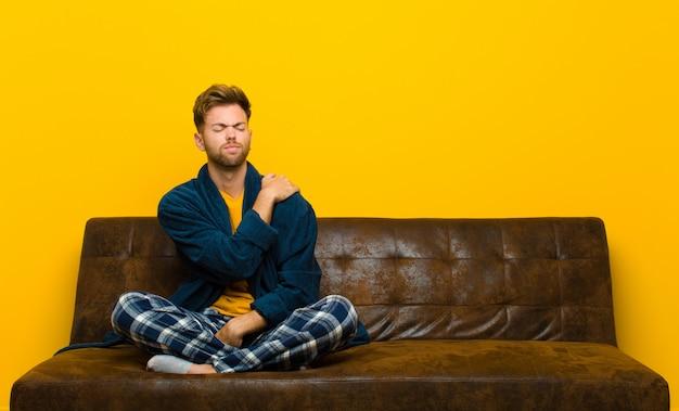 Tragende pyjamas des jungen mannes, die betontem besorgtem frustriertem und niedergedrücktem leiden mit rücken- oder nackenschmerzen müde sich fühlen. auf einem sofa sitzen