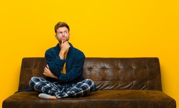 Tragende pyjamas des jungen mannes, die das fühlen zweifelhaft und verwirrt mit den verschiedenen wahlen sich wundernd denken, welche entscheidung zu treffen ist. auf einem sofa sitzen