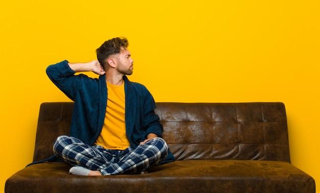 Tragende pyjamas des jungen mannes, die denken oder zweifeln, kopf verkratzen, verwirrt und verwirrt fühlen, hintere oder hintere ansicht. auf einem sofa sitzen