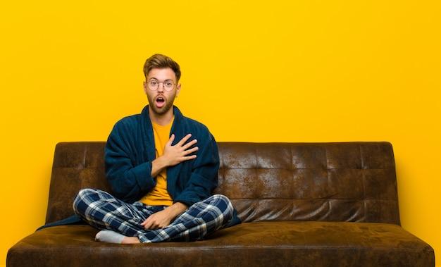 Tragende pyjamas des jungen mannes, die entsetzt und überrascht sich fühlen, lächelnd und nehmen hand zum herzen, glücklich, die oneshowing dankbarkeit zu sein. auf einem sofa sitzen