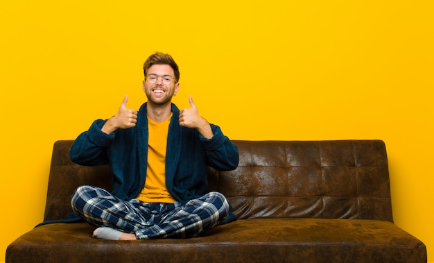 Tragende pyjamas des jungen mannes, die glücklich, positiv, überzeugt und erfolgreich, mit beiden daumen oben breit schauen lächeln. auf einem sofa sitzen