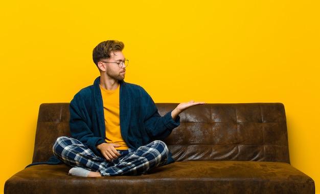 Tragende pyjamas des jungen mannes, die glücklich sich fühlen und zufällig lächeln, schauend zu einem gegenstand oder zu einem konzept, die auf der hand auf der seite gehalten werden