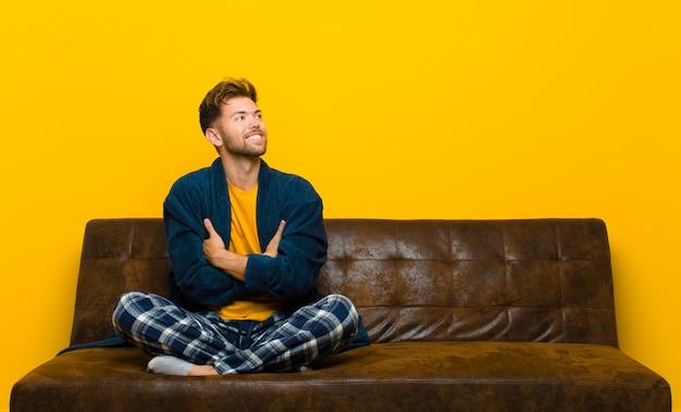 Tragende pyjamas des jungen mannes, die glücklich stolz und hoffnungsvoll sich wundern oder denken, oben schauend, um raum mit den gekreuzten armen zu kopieren. auf einem sofa sitzen