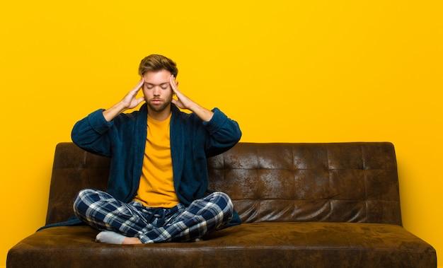 Tragende pyjamas des jungen mannes, die konzentriert, durchdacht und angespornt schauen, mit den händen auf stirn gedanklich lösen und sich vorstellen. auf einem sofa sitzen