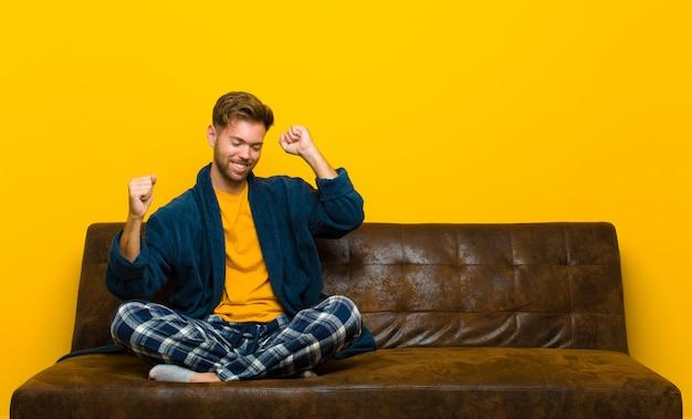 Tragende pyjamas des jungen mannes, die lächeln, sorglos, entspannt und glücklich sich fühlen, musik tanzen und hören und spaß an einer party haben. auf einem sofa sitzen