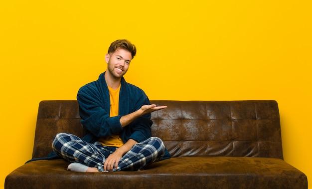 Tragende pyjamas des jungen mannes, die nett lächeln, sich glücklich fühlen und ein konzept im kopienraum mit palme der hand zeigen. auf einem sofa sitzen