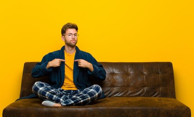 Tragende pyjamas des jungen mannes, die stolz, positiv und das zufällige zeigen auf kasten mit beiden händen schauen. auf einem sofa sitzen