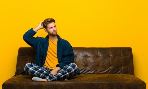 Tragende pyjamas des jungen mannes, die verwirrt und verwirrt sich fühlen, kopf verkratzen und zur seite schauen. auf einem sofa sitzen