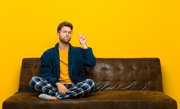 Tragende pyjamas des jungen mannes, die wie ein genie sich fühlen, das stolz finger in der luft hält, nachdem eine großartige idee verwirklicht worden ist und eureka gesagt hat. auf einem sofa sitzen