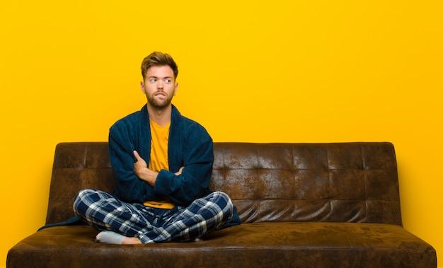 Tragende pyjamas des jungen mannes, die zweifeln oder denken, lippe beißen und unsicher und nervös sich fühlen und schauen, um raum auf der seite zu kopieren