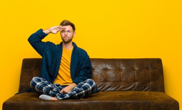 Tragende pyjamas des jungen mannes mit einem militärgruß in einer tat der ehre und des patriotismus, respekt zeigend. auf einem sofa sitzen